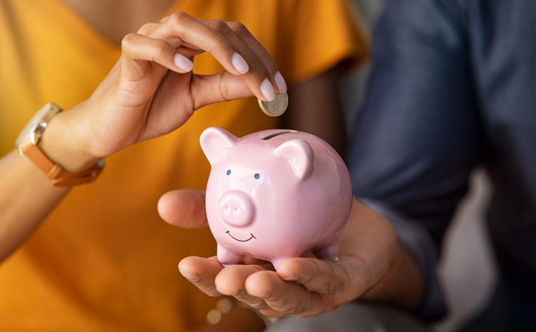Couple saving money in piggybank